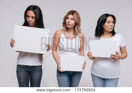 No eye contact. Thoughtful remarkable independent ladies acting on set of a new social campaign while posing for a photographer holding up blank signs