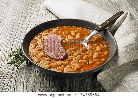 White bean stew with fresh spices and sausage on wooden table