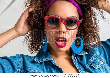 Portrait of Cheerful african female with blue eye makeup expressing her passion. She is wearing sunglasses and big earrings