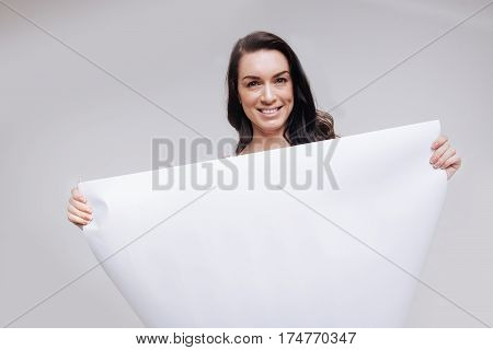 Everything white. Gorgeous passionate graceful lady holding a big white sign while standing isolated on white background and smiling