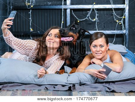 Woman doing self photo in bed with big black doberman dog