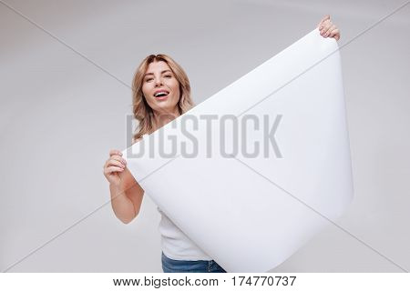 Lively and positive. Inspiring joyful magnetic lady looking full of hope while posing with a blank poster and standing isolated on white background
