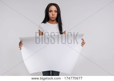 You should know about this. Graceful powerful gorgeous woman holding up a big white sing while working on social campaign and posing for a photographer