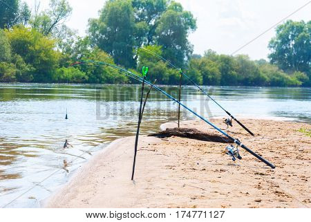Fishing rod on the bank of the river on a background of blue sky.