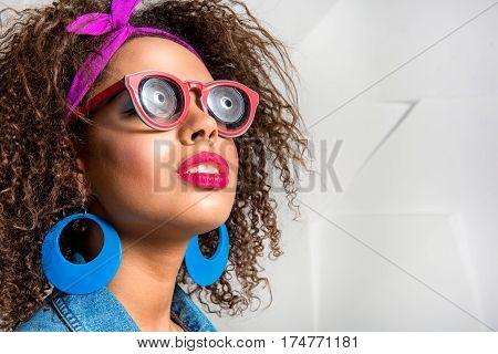 Calm african female looking up with interest. She has curly hair and wearing sunglasses and big earrings. Copy space