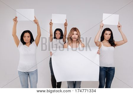 Stand with us. Graceful stunning modern ladies working for a social advertisement while posing for professional photographer and standing isolated on white background