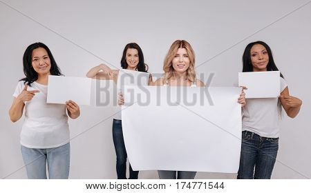 Big enough to read. Magnificent charming young women holding blank pieces of paper different in size while posing for social campaign in a studio