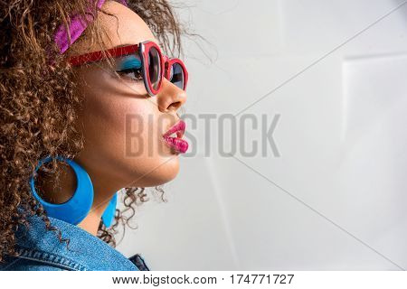 Serious african female with curly hair looking forward with interest. She dressing sunglasses and big earrings. Copy space