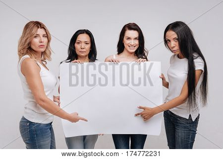 We are here for a cause. Inspirational strong gorgeous ladies demonstrating a big blank poster while posing in a studio standing isolated on white background