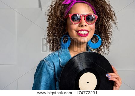Portrait of Beaming young woman wearing sunglasses and holding music platter in arm. She is smiling