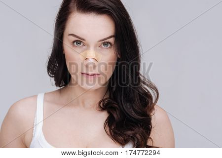 Do I really need this. Sensual serious amazing lady taking part in social campaign promoting natural beauty while wearing a patch on her nose