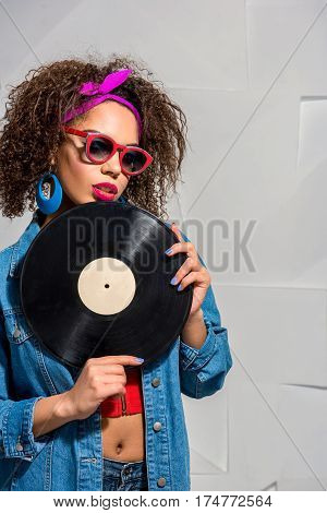 Calm woman wearing sunglasses and earrings keeping gramophone record in arm