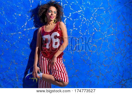 Portrait of cheerful young woman keeping her jogging shoes while leaning against one-coloured background. She is laughing. Copy space