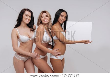 We are all stunning. Radiant feminine curvy women looking delighted while working together on a social campaign and posing in their lingerie