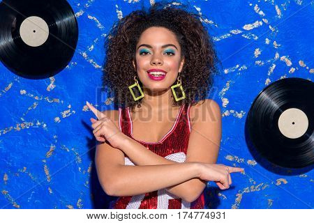 I like disco. Happy young woman with curly hair and blue makeup dancing while situating opposite phonograph records