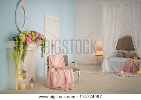 Fireplace decorated with flowers and candles. Beige couch by the fireplace decorated with light pink blanket