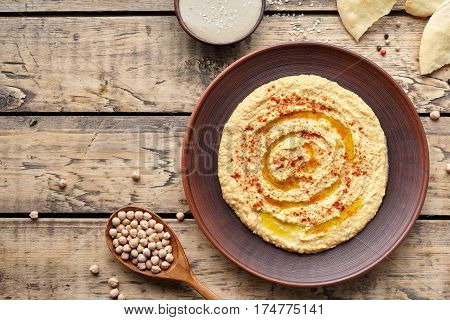 Hummus traditional snack chickpea vegan natural nutrition lunch dip paste with paprika tahini and olive oil in clay plate on rustic flat lay. Healthy dietary fiber protein food