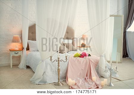 Bed with a white canopy. Romantically decorated bedroom light colors, flower petals and candles.
