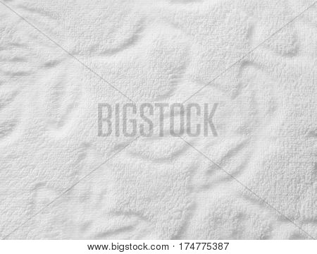 White furry fabric with floral ornament. Close up.