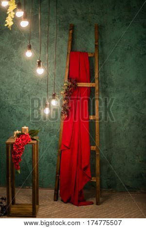 Romantic fotozona in red and green colors for photo shoots in the style loft, decorated with flowers and lights. Wedding style loft.
