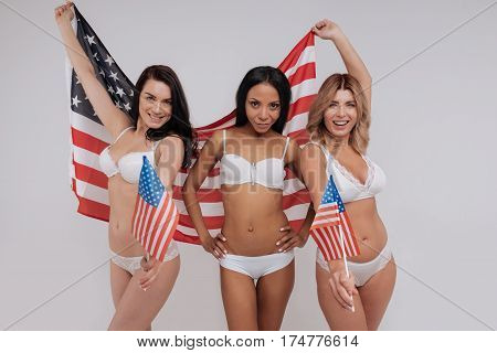 We are the best. Seductive feminine glamorous ladies posing in their lingerie and holding a flag demonstrating unity of differences