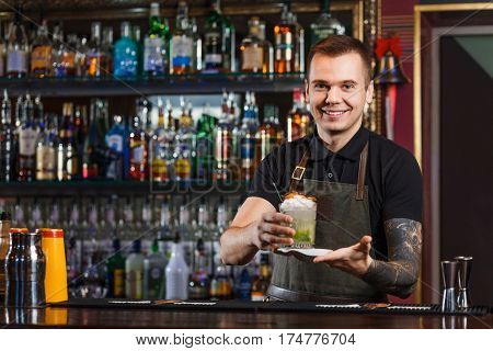Cheerful bartender gives the cocktail to customer. Focus on face.