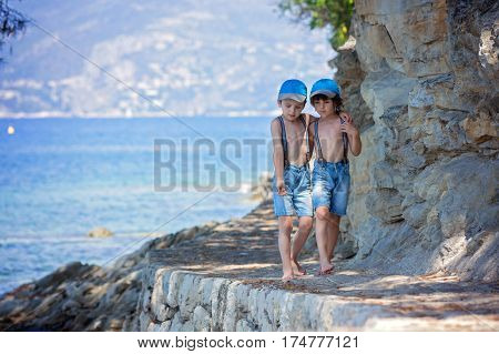 Two Children, Boy Brothers, Walking On A Path Around Mediterranian Sea On French Riviera