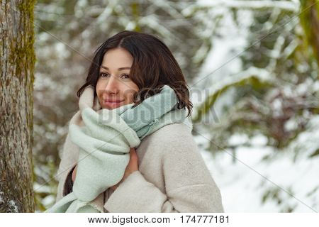 Waist up portrait of outgoing attractive young woman standing near trees in forest in winter in Oregon