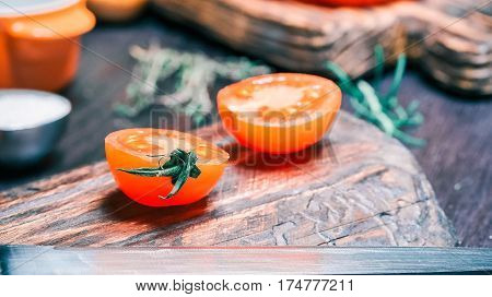 Fresh red cherry tomatoes, rosemary and salt on wood cutting board and on black table. Close-up