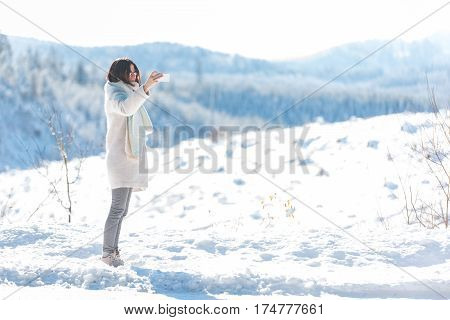 Outgoing woman taking photos with mobile while standing in snow in United States