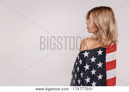 Gorgeous patriot. Classy dreamy blonde lady posing during a national beauty campaign while wearing a flag over her shoulders and looking stunning