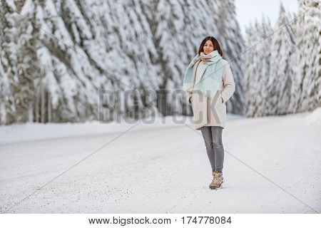 Outgoing young woman standing opposite tall fluffy pines near road in winter in United States
