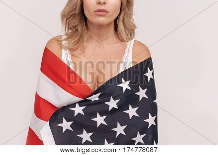 Stars and stripes. Curvy enigmatic real woman posing for a photographer while wearing her underwear and standing isolated on white background