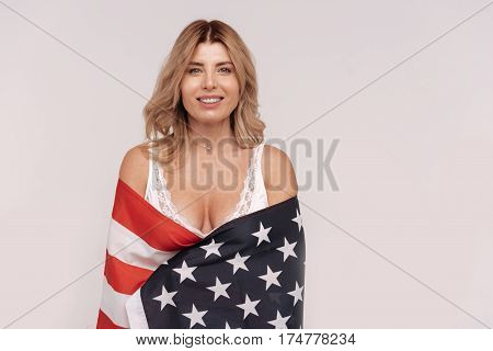 Feeling proud. Hypnotic joyful radiant lady standing isolated on white background being wrapped up in a national flag