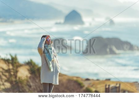 Cheerful young female looking at distance while standing on coastline in Oregon