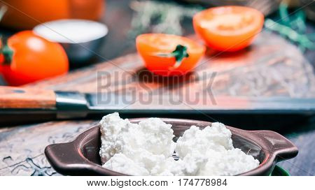 Red cherry tomatoes on wood board, chefs knife and farmer cheese in ceramic plate on black table. Close-up