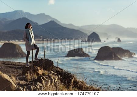 Cheerful young woman standing opposite clear blue ocean washing big stones. Cannon beach