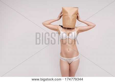 Faceless beauty. Delicate thin determined lady promoting tolerance while posing in her underwear and wearing a paper bag on her head