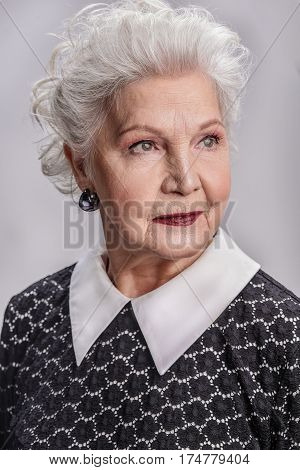 Wisdom and grace. Portrait of beautiful mature woman with wise and warm smile looking aside isolated on gray background