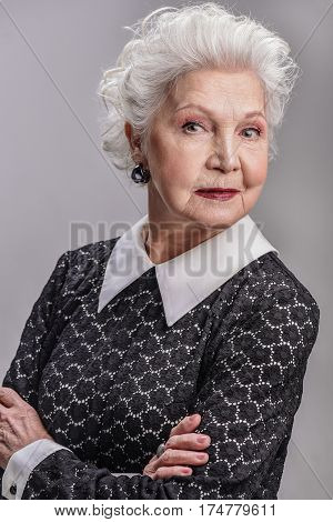 I am going to be me today. Waist up portrait of elderly stylish female standing with her arms folded, isolated on gray background