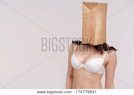 I am not an object. Devoted fit female activist promoting tolerance in society while posing with her face covered and standing isolated on white background