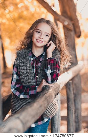 Beautiful teenage girl 12-14 year old posing outdoors. Wearing fur vest checkered shirt. Looking away.