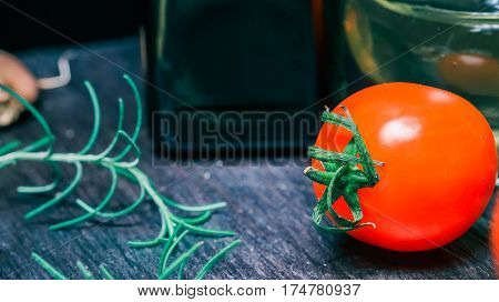 Fresh red cherry tomatoes and  on dark wood cutting board and on black table. Close-up