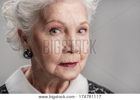 I will never forget. Portrait of thinking elderly female posing isolated on gray background