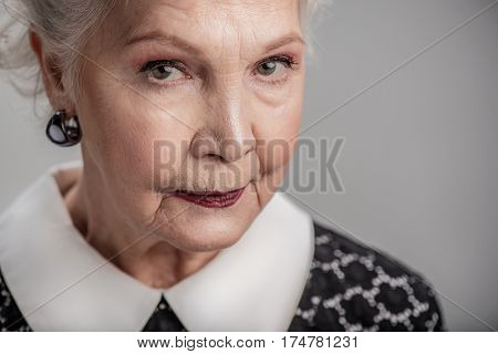 She takes life very seriously. Close up portrait of beautiful middle aged woman with white hair and fresh makeup isolated gray background