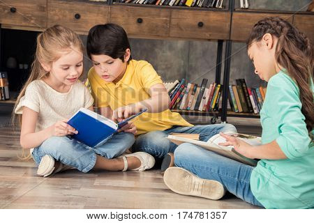 concentrated boy and girls reading books in library