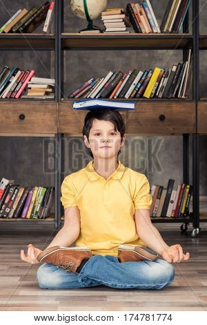 boy with book on head sitting in lotus pose in library