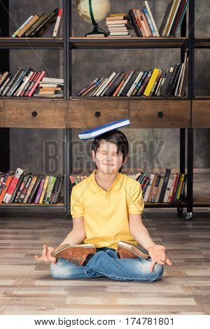 smiling boy with book on head sitting in lotus pose in library