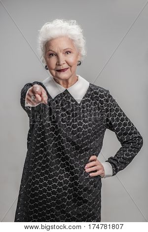 Let your age grow old but not your heart. Portrait of grey haired senior woman posing while pointing at viewer with confidence. Isolated on gray background