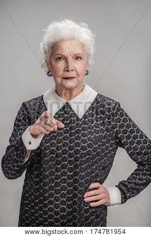 Just look at this. Portrait of Serious middle aged lady looking and pointing to camera. isolated on gray background